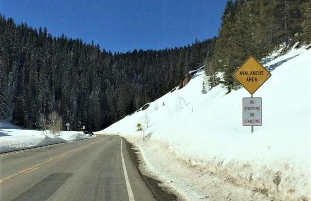 This caution sign indicates an avalanche area and advises that there is no stopping or standing at the location. Backcountry users are urged to watch for these signs and never park vehicles or trailers on the side of the road at these sites.